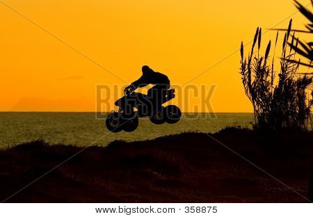 Quad Bike Jumping On Beach At Sunset In Spain