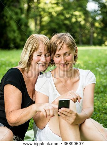 Mature mother and daughter with smartphone
