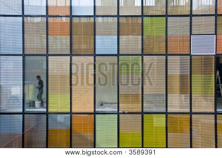 Man Painting Behind Colorful Office Windows