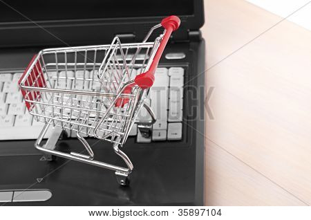Online shopping. trolley on laptop