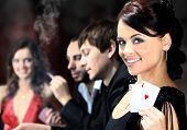 stock photo of poker hand  - Poker players sitting around a table at a casino - JPG