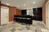 foto of basement  - Bar in basement of luxury home with dark wood cabinetry - JPG