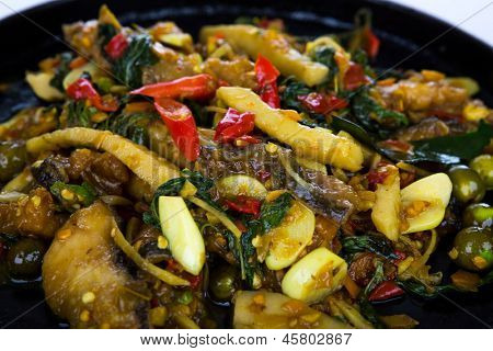 Fried fish with fresh herbs and  spicy sauce served on iron hot plate
