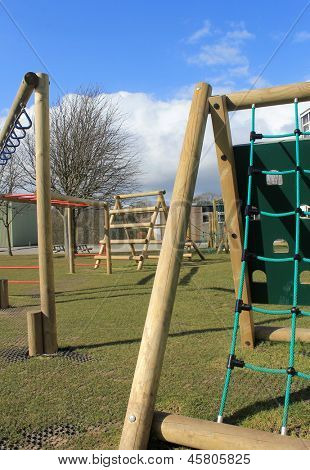School climbing frame with playground and sports hall in background, Scarborough, England.