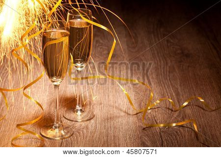 Flutes of champagne in holiday setting on the wooden background , Closeup.