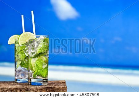 Cocktail mojito ice lemon straws in tropical beach Islands against a background