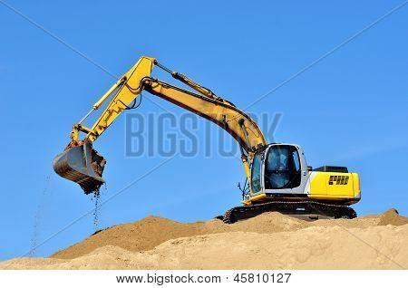 nova escavadeira amarela trabalhando em dunas de areia