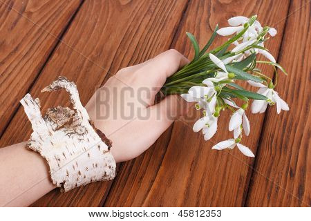 Snowdrops in a female hand with a bracelet on a birch