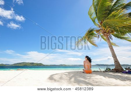 young girl sitting on beach under coconut tree
