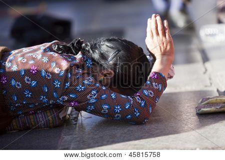 LHASA, TIBET-Oktober 08: A tibetischen weiblichen buddhistische Pilger in vollen Boden Niederwerfung in beten ist