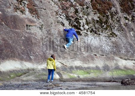 Guy Scaling Rock