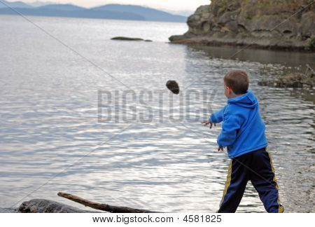 Little Boy Throwing A Big Rock In Ocean
