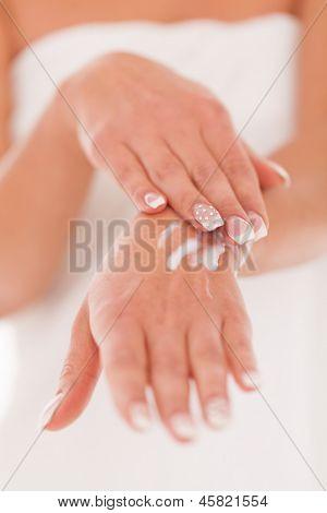 Beautiful woman massage herself with white cream