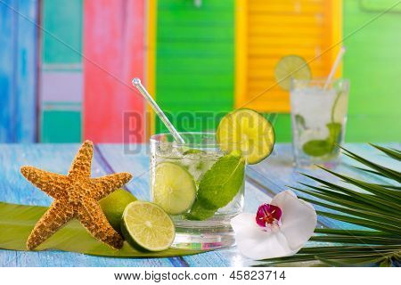 Cuban Mojito cocktail in tropical colorful house on blue wood with flowers and starfish
