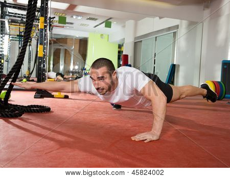 Crossfit fitness man balance push ups with one leg and arm up exercise at gym workout
