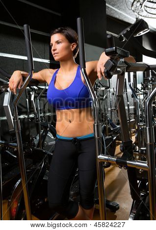elliptical walker trainer woman posing at black gym relaxed after aerobics exercise