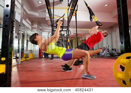 Crossfit fitness TRX training exercises at gym woman and man push-ups workout