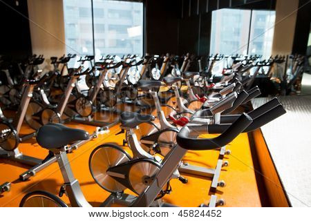 Aerobics spinning exercise bikes gym room with many in a row