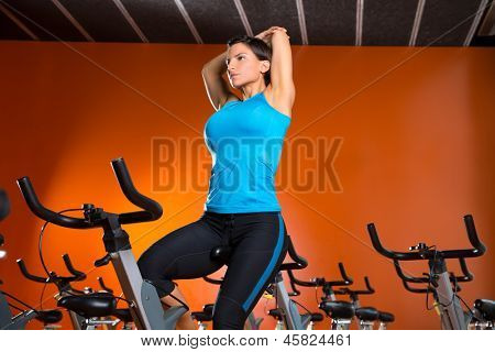 Aerobics spinning woman stretching exercises after workout at gym