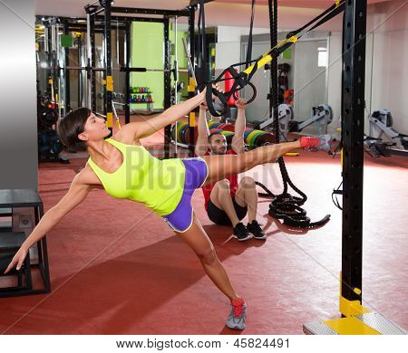 Crossfit fitness TRX training exercises at gym woman and dip rings man workout