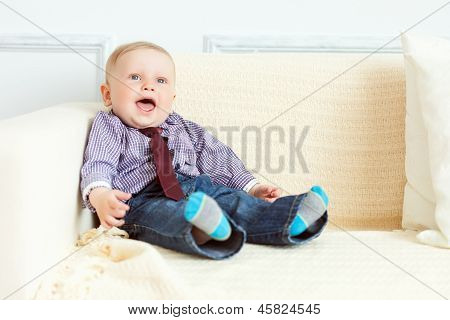 Boy in suit is sitting on sofa