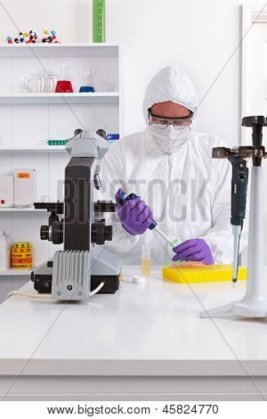 A lab technician in sterile clothing using a pipette