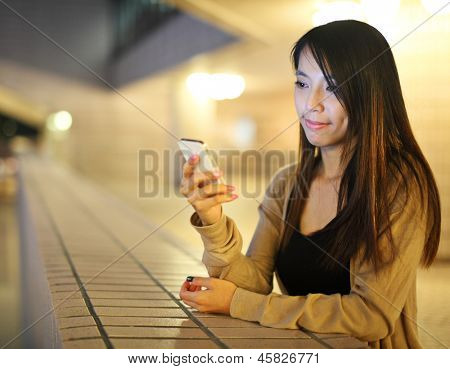 Asian woman using smartphone at night
