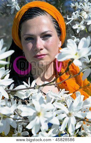 Blue-eyed woman among of magnolia