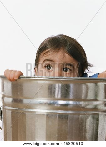 Toddler girl peering over rim of metal bucket