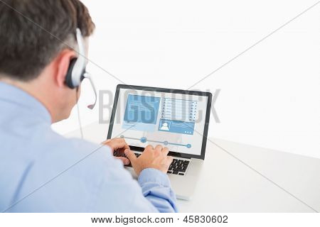 Call center worker viewing his social media profile on laptop at desk