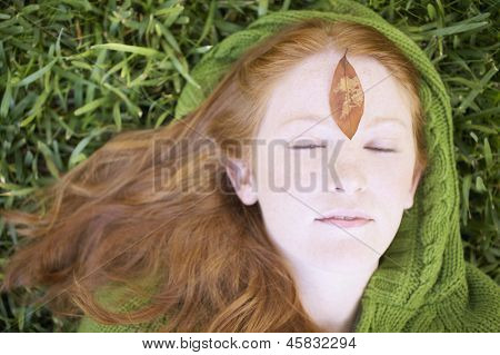 Close up of young woman lying on grass
