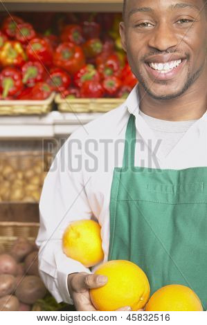 Male supermarket worker with fruits
