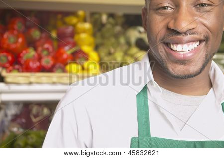 Male supermarket worker smiling
