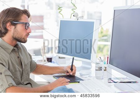 Graphic artist using graphics tablet at his desk