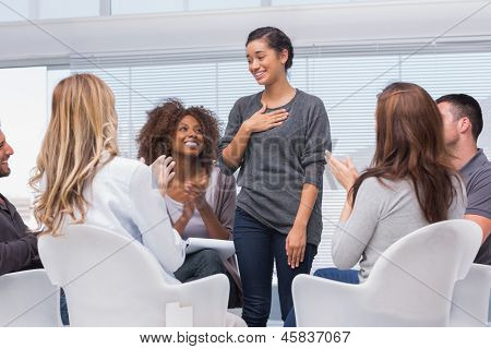 Happy patient has a breakthrough in group therapy while others are clapping her