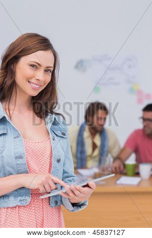 Editor using tablet  and smiling as team works behind her at desk