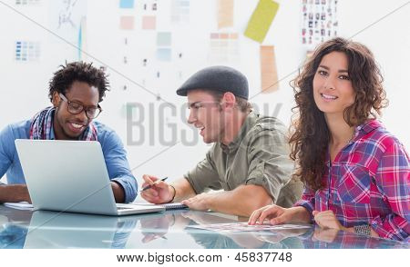 Team of editors at work with one smiling at camera in modern creative office