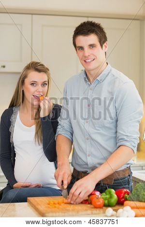 Pregnant woman eating vegetables prepared by husband in kitchen