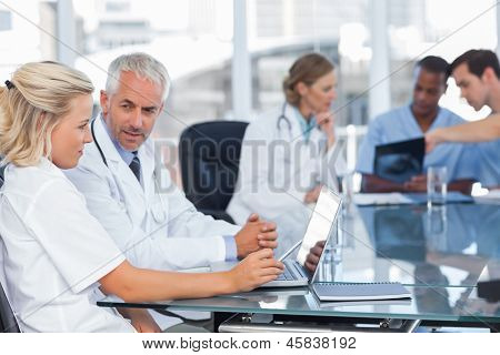 Two doctors using laptop in front of medical team analysing radiography