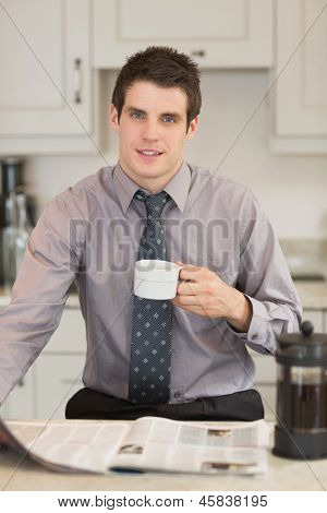 Man reading newspaper while drinking coffee in kitchen