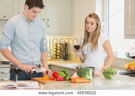 Man cooking with woman drinking red wine in kitchen
