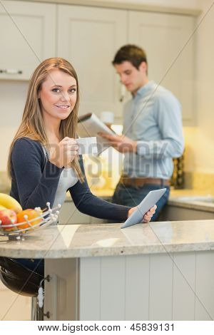 Woman drinking coffee and holding tablet pc in kitchen