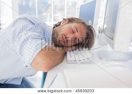 Man sleeping on his desk in bright modern office