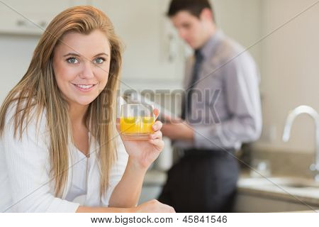 Young woman drinking orange juice in kitchen with husband reading newspaper