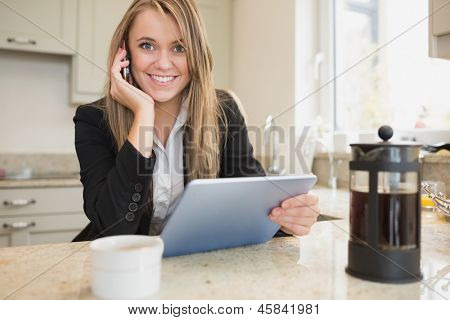 Smiling woman with tablet and mobile phone in kitchen