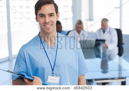Young doctor holding a file and standing in front of his team