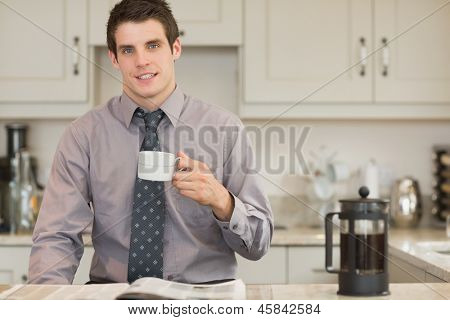 Man drinking coffee while reading newspaper in kitchen