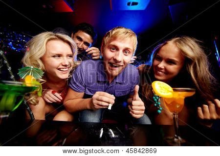 Image of young guy with cocaine surrounded by two laughing girls in night club