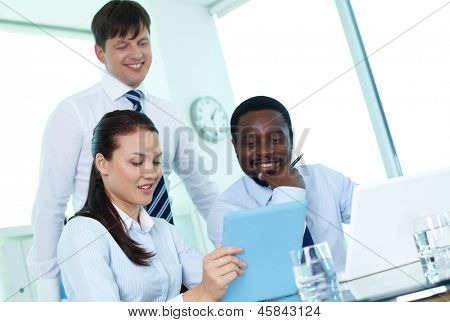 Male colleagues listening to young employee making electronic presentation at meeting