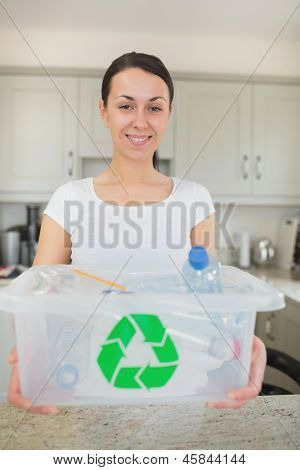 Woman holding full recycling bin in kitchen